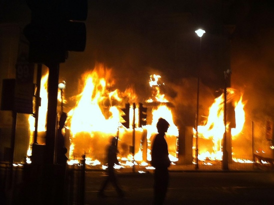 LONDON, ENGLAND - AUGUST 06:  A Carpetright store burns on Tottenham High Road after being set on fire by youths protesting against the killing of a man by armed police in an attempted arrest, August 6, 2011 in London, England. Twenty-nine-year-old father-of-four Mark Duggan died August 4 after being shot by police in Tottenham, north London.  (Photo by Matthew Lloyd/Getty Images)